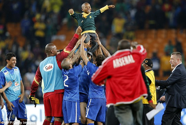 Picture of pride: The boy looks delighted in Soweto as the superstars show their kind side