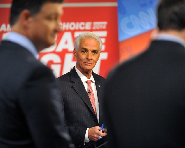 Democratic candidate Charlie Crist, center, waits for a question before his live debate with Republican Gov. Rick Scott, Tuesday, Oct. 21, 2014 hosted by WJX...