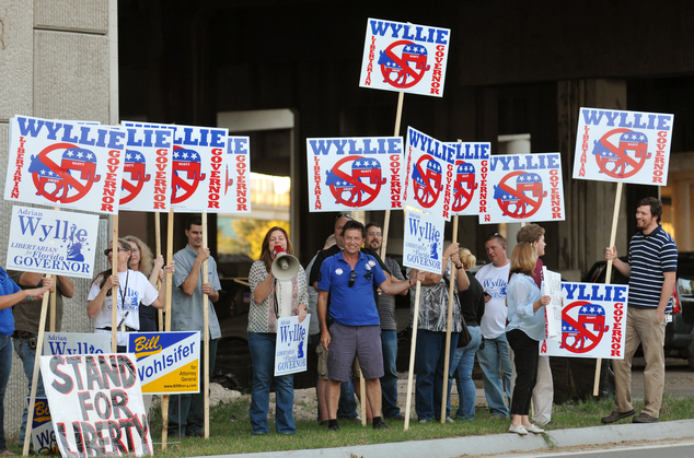 Supporters of Libertarian candidate Adrian Wyllie protest before the live debate between Democratic candidate Charlie Crist and Republican Gov. Rick Scott, T...