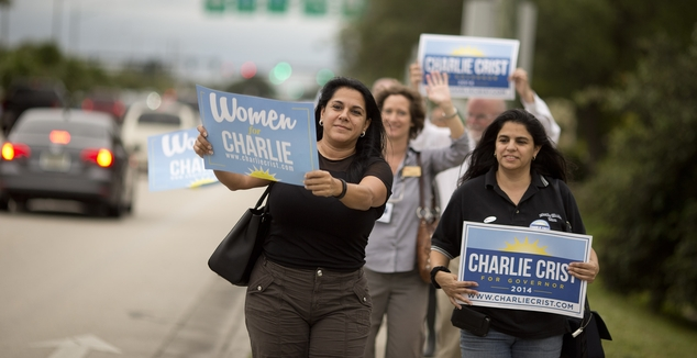 Crist for Governor Campaign supporters walk a sidewalk in Davie, Fla., before an Early Vote rally Tuesday, Oct. 21, 2014. Following the early vote event, Dem...