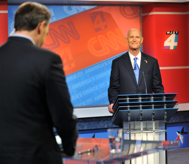 Republican Gov. Rick Scott waits for a question before his live debate with Democratic challenger Charlie Crist, Tuesday, Oct. 21, 2014 hosted by WJXT-TV and...