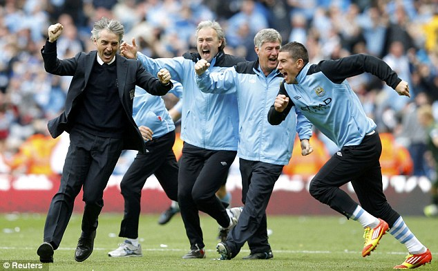 Sky Blue heaven: Mancini (left) runs onto the pitch after securing the title