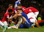 A dejected Gary Cahill of Chelsea as Robin van Persie of Manchester United celebrates after scoring a goal to make it 1-1