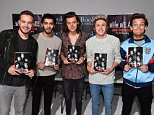 One Direction holding copies of their autobiography 'One Direction: Who We Are'