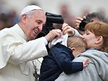 Pope Francis greets a child who hides himself after his general audience at St Peter's square on October 29, 2014 at the Vatican.   AFP PHOTO / GABRIEL BOUYSGABRIEL BOUYS/AFP/Getty Images