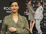 Rihanna holds the pregnant belly of Spc. Ariel Evans during an event promoting her Rogue Man cologne at Ft. Belvoir Exchange on Wednesday, Nov. 12, 2014 in Ft. Belvoir, Va. (AP Photo/Kevin Wolf)