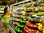 Woman selecting mushrooms in the produce section of a food store.