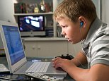 Young boy in bedroom using laptop and listening to MP3 player. Image shot 2008. Exact date unknown. B9TFC2  Working, Music, listening, music, Technology, Game, Games, Time, children, listening, music, Technology, Game, Games, Time, children