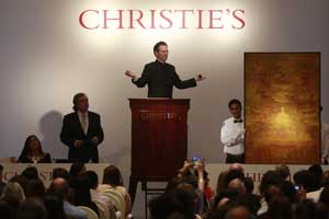 Christie's International Director, Asian Art, Hugo Weihe, center, acts as auctioneer for the painting of Indian artist Vasudeo S. Gaitonde during Christie's first auction in India. (PTI photo)