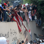 Protesters destroy an American flag pulled down from the U.S. embassy in Cairo, Egypt, on Sept. 11, 2012. (AP Images)