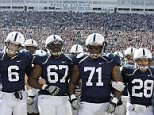 Penn State players Derek Moye (6), Quinn Barham (67), Devon Still (71), and Drew Astorino (28) link arms as they lead the team onto the field before an NCAA college football game against Nebraska in State College, Pa., Saturday, Nov. 12, 2011. (AP Photo/Gene J. Puskar)