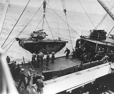 Men hoist out No. 835, a marine landing vehicle tracked (LVT), from Hansford (APA-106), February 1945. LVT(A)4s such as this vehicle, armed with M3 75 millimeter howitzers or Canadian Ronson flamethrowers, support the marines fighting the Japanese on Iwo Jima.
