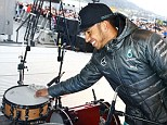 Hamilton inspects the drum kit on stage at Mercedes' Stars and Cars event in Stuttgart, Germany