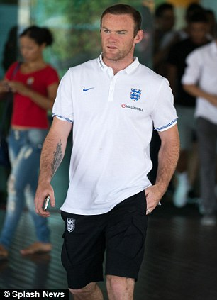 Day off: Steven Gerrard and Wayne Rooney take a stroll through a local shopping centre in Manaus