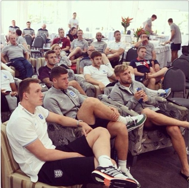 Watching brief: Englands' players and staff gather round to see Brazil beat Croatia 3-1