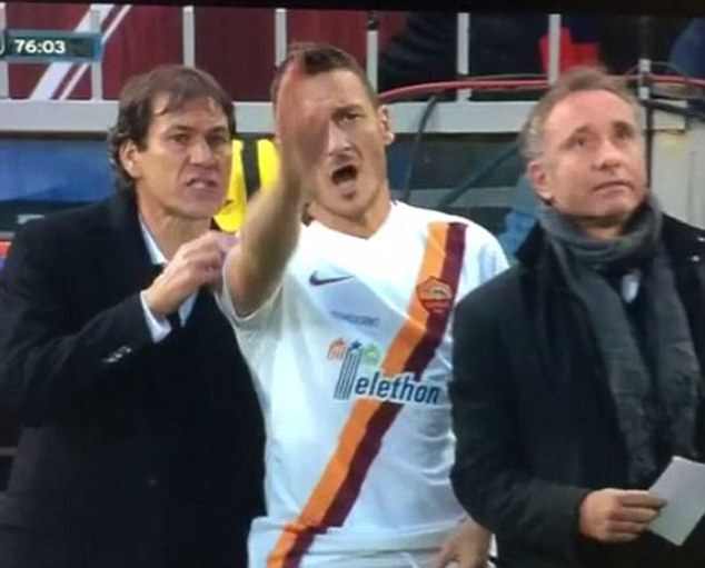 Francesco Totti stands on the touchline ready to come on for Roma but didn't appear to be in a good mood