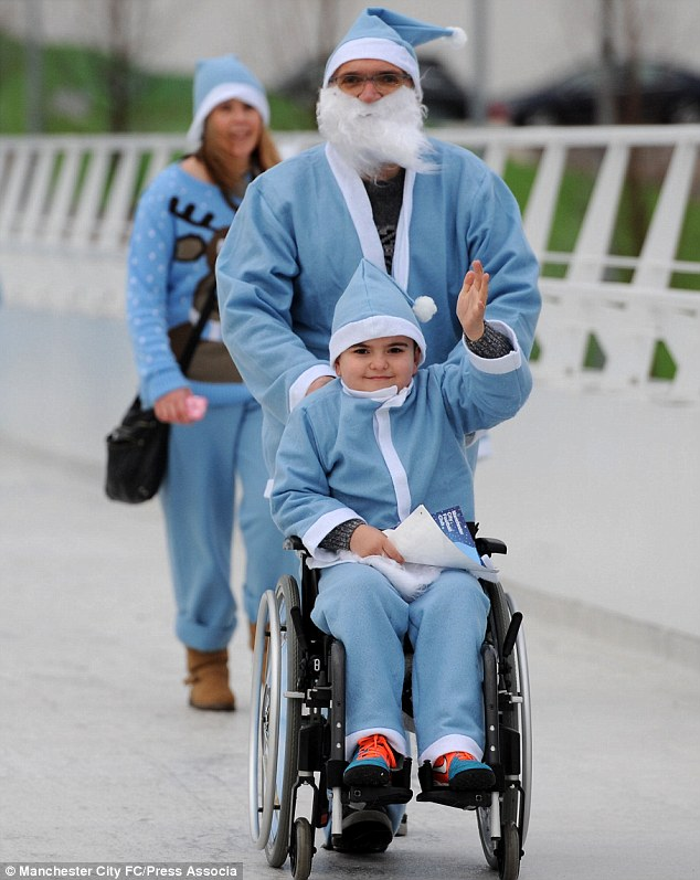 One City fans in a wheelchair is guided around the Etihad Campus - both of them dressed as Santa