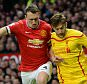 Manchester United's English defender Phil Jones (L) vies with Liverpool's English midfielder Adam Lallana during the English Premier League football match between Manchester United and Liverpool at Old Trafford in Manchester, north west England, on December 14, 2014. AFP PHOTO / OLI SCARFF RESTRICTED TO EDITORIAL USE. No use with unauthorized audio, video, data, fixture lists, club/league logos or live services. Online in-match use limited to 45 images, no video emulation. No use in betting, games or single club/league/player publications.OLI SCARFF/AFP/Getty Images
