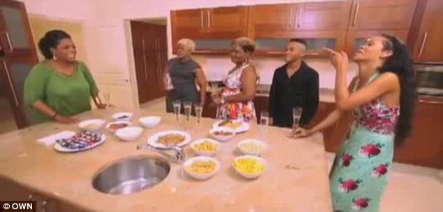 Normal life: Rihanna and Oprah quaff champagne in the kitchen with some of the singer's relatives