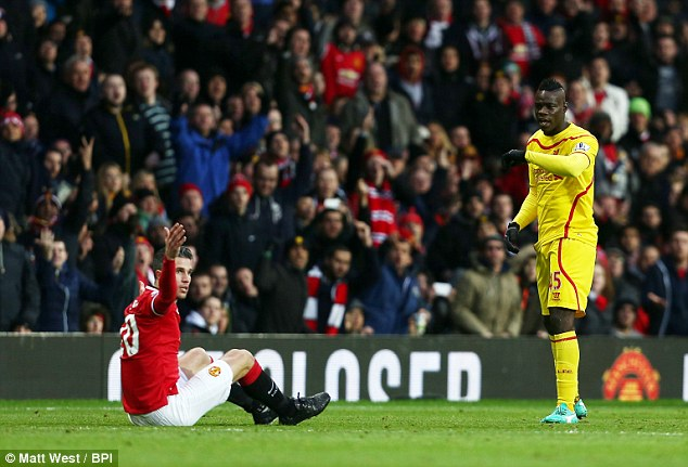 Balotelli (right) should have been booked for a pulling down Robin van Persie (left) on 52 minutes