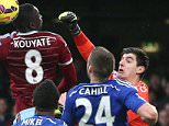 Thibaut Courtois of Chelsea punches clear from Cheikhou Kouyate of West Ham United