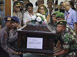 "A relative, center, weeps as Indonesian soldiers lift a coffin containing the body of Hayati Lutfiah, one of the victims of AirAsia Flight 8501, during the handover ceremony to her family at the police hospital in Surabaya, East Java, Indonesia, Thursday, Jan. 1, 2015. Searchers were racing ""against time and weather"" Thursday to recover the dead from the crash, with a window of good conditions slammed shut by another onslaught of wind and heavy rain. (AP Photo/Dita Alangkara)"
