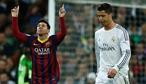 Messi (left) points to the sky after scoring against Real Madrid during a La Liga match in March 2014
