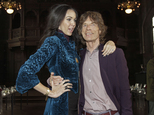 FILE - This Feb. 16, 2012 file photo shows singer Mick Jagger, right, with designer L'Wren Scott after her Fall 2012 collection was modeled during Fashion Week, in New York. Jagger has established a scholarship in honor of his late girlfriend, fashion designer Scott. The scholarship will allow one master¿s degree student per year over a period of three years to attend the elite Central Saint Martins, the London-based college announced this weekend. (AP Photo/Richard Drew, File)