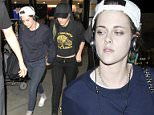 Kristen Stewart & her girlfriend Alicia Cargile hold hands as Cargile shows off her Star of David tattoo on her stomach.  The adorable couple were seen arriving at LAX in Los Angeles surrounded by bodyguards.   Pictured: Kristen Stewart, Alicia Cargile Ref: SPL943917  050215   Picture by: Sharky / Splash News  Splash News and Pictures Los Angeles: 310-821-2666 New York: 212-619-2666 London: 870-934-2666 photodesk@splashnews.com