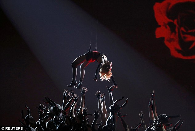 'Love lift me': Madonna finished her song by being pulled up into the air, suspended above her dancers
