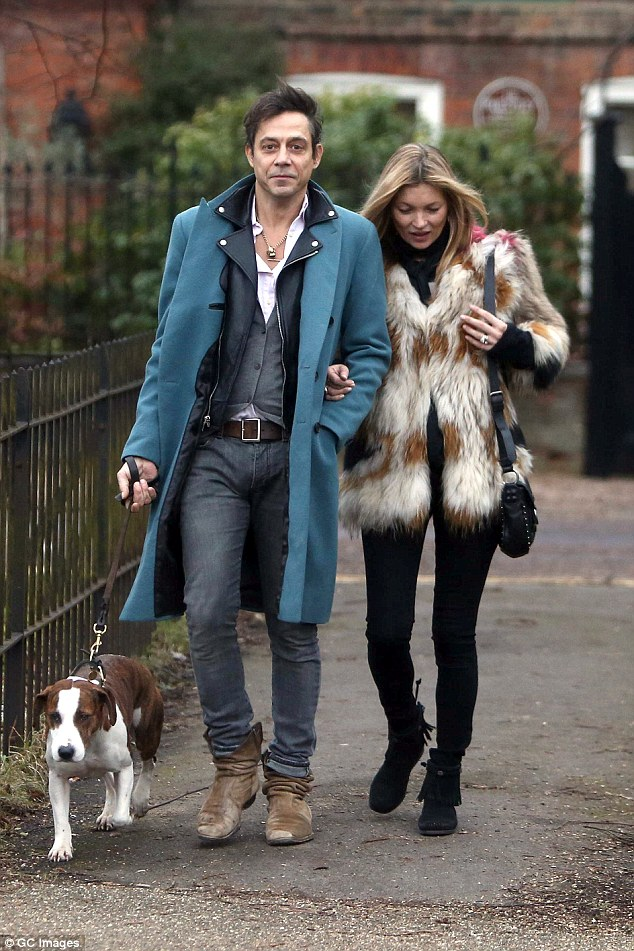 Not alone:Accompanied by their pet dog, the loved-up couple appeared to be in blissful spirits as they cuddled up to one another during their stroll in London