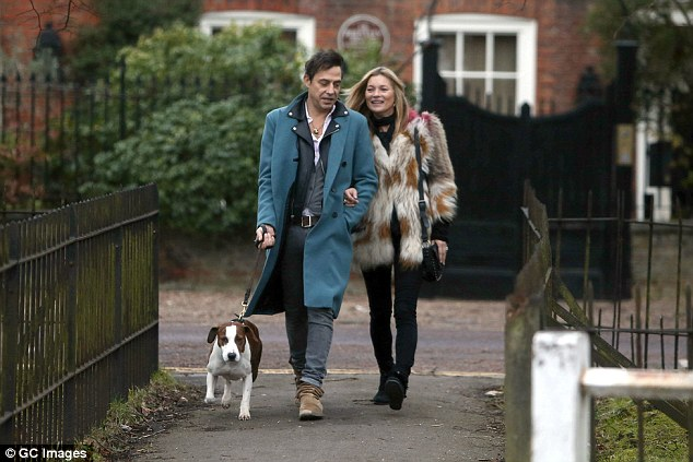 City chic: The 41-year-old star looked every inch the supermodel in a glamorous off-white fur jacket, complete with colourful detailing,while Jamie cut a stylish figure in a teal coloured overcoat
