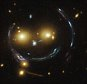 In the centre of this image, taken with the NASA/ESA Hubble Space Telescope, is the galaxy cluster SDSS J1038+4849 ¿ and it seems to be smiling. You can make out its two orange eyes and white button nose. In the case of this ¿happy face¿, the two eyes are very bright galaxies and the misleading smile lines are actually arcs caused by an effect known as strong gravitational lensing. Galaxy clusters are the most massive structures in the Universe and exert such a powerful gravitational pull that they warp the spacetime around them and act as cosmic lenses which can magnify, distort and bend the light behind them. This phenomenon, crucial to many of Hubble¿s discoveries, can be explained by Einstein¿s theory of general relativity. In this special case of gravitational lensing, a ring  ¿ known as an Einstein Ring  ¿ is produced from this bending of light, a consequence of the exact and symmetrical alignment of the source, lens and observer and resulting in the ring-like structure we see h