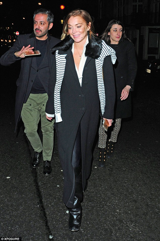 What problems? Lindsay Lohan looked carefree as she enjoyed a night out with pals in London on Monday