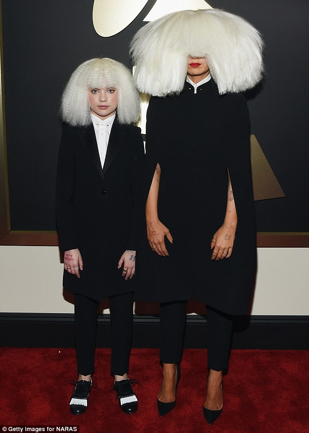 Making an entrance: She arrived to the 57th Grammy awards ceremony in a large blonde wig covering her entire face along with Dance Moms starMaddie Ziegler