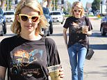 Emma Roberts grabs coffee in sleek sunglasses and snakeskin shoes wearing a vintage tee in Los Angeles before smiling as she gets back to her cat February 9, 2015 X17online.com