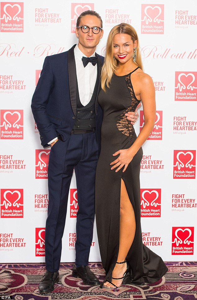 Made in heaven: Reality star Ollie Proudlock looked dapper in a navy tuxedo while he proudly posed alongside his stunning girlfriendEmma Louise Connolly, who showed some leg in a halterneck dress with a split to the thigh