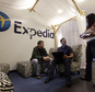 FILE - In this Tuesday, Jan. 15, 2013, file photo, Expedia analytics team workers Mike Brown, left, Saurin Pandya and Prashanti Tata chat in an alcove set up for employees, in Bellevue, Wash. Expedia announced on Thursday, Feb. 12, 2015, that it is buying rival online travel site Orbitz for approximately $1.33 billion. The deal comes less than a month after Expedia announced the $280 million acquisition of another rival, Travelocity. (AP Photo/Elaine Thompson, File)