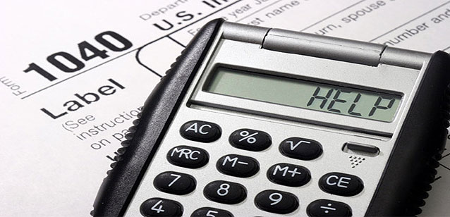 Picture of a calculator whose digits spell out the word HELP, sitting on top of an IRS form 1040.