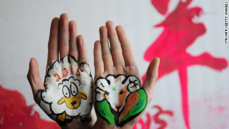 This photo taken on December 30, 2014 shows college students with paintings of sheep on their hands to welcome the new year, and to mark the coming 'Year of the Sheep', in Liaocheng, in eastern China's Shandong province. The Year of the Sheep, according to the lunar new year calendar, will start on February 19, 2015. CHINA OUT AFP PHOTO (Photo credit should read STR/AFP/Getty Images)