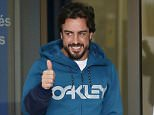 McLaren's Formula One driver Fernando Alonso of Spain gestures to the media as he leaves a hospital where he has been hospitalized since Sunday, in Sant Cugat, north of Barcelona February 25, 2015. McLaren have blamed gusting winds for Alonso's Formula One testing crash on Sunday and dismissed 'erroneous rumours' that an electrical fault could have rendered the driver unconscious before the impact.    REUTERS/Albert Gea (SPAIN - Tags: SPORT MOTORSPORT PROFILE F1)