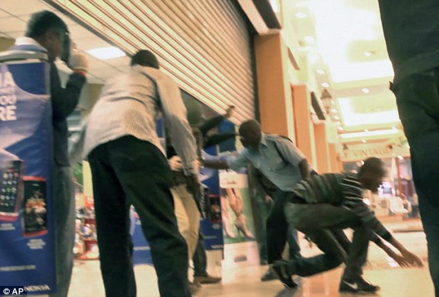 Rescued: Undercover police officers and police with guns asking shoppers caught up in the incident to leave with their hands up as they crouch on the ground for cover