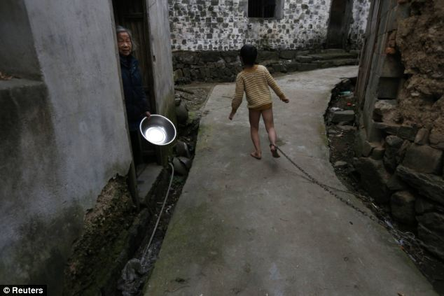 Chained: Eleven-year-old He Zili runs past a neighbour along an alley outside his home