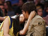 Musician Anthony Kiedis of the Red Hot Chili Peppers, right, and Brazilian fashion model Wanessa Milhomem kiss as they sit courtside during the second half of an NBA Basketball game between the Los Angeles Lakers and Atlanta Hawks, Sunday, March 15, 2015, in Los Angeles. The Hawks won 91-86. (AP Photo/Danny Moloshok)
