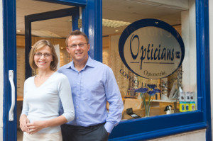 Couple standing in front of their Optician Store