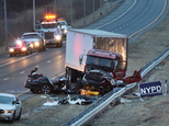 Police investigate the crash scene between a truck and a car carrying four people in the Staten Island borough of New York, Friday, March 20, 2015. The car, driving the wrong way and carrying three off-duty officers with the Linden, N.J. police department, crashed into the truck, killing one officer and another person and leaving two other officers critically injured, officials said. The truck driver was treated for injuries that weren't considered to be life-threatening. (AP Photo/Staten Island Advance, Irving Silverstein)  MANDATORY CREDIT