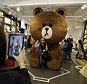 In this March 16, 2015 photo, tourists take their souvenir photos with an outsized Lineís character Brown bear at the Line Friends flagship shop in Seoul, South Korea. For smartphone users in Asia where most of Lineís 181 million monthly users are located, the characters are as familiar as Hello Kitty or Disneyís animated stars. They are not well known in America or Europe but owner Line Corp. hopes to change that. It plans to open 100 stores selling Brown dolls and other cute ìLine Friendsî paraphernalia worldwide over the next three years as a way to draw more users to the app. (AP Photo/Lee Jin-man)