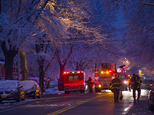 Firefighters walk near the scene of a fire, center left, in which seven children died in the Brooklyn borough of New York Saturday, March 21, 2015. (AP Photo/Craig Ruttle)
