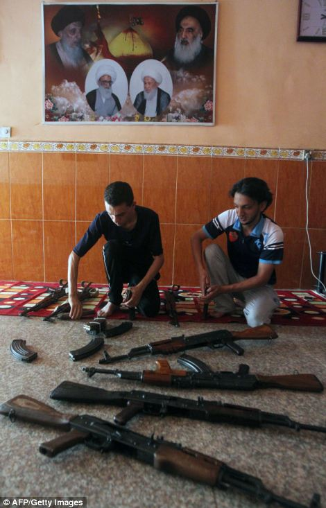 Iraqi men clean weapons as they get ready to defend their Sadr City district in case of an attack by Sunni extremists