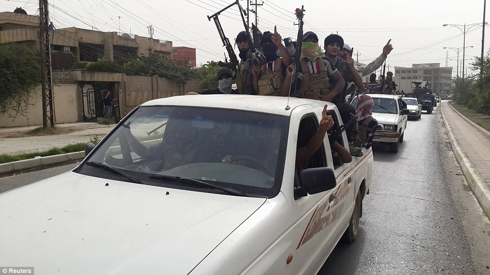 Marauders: Fighters of the Islamic State of Iraq and the Levant celebrate on American Humvees taken from Iraqi security forces along a street in city of Mosul
